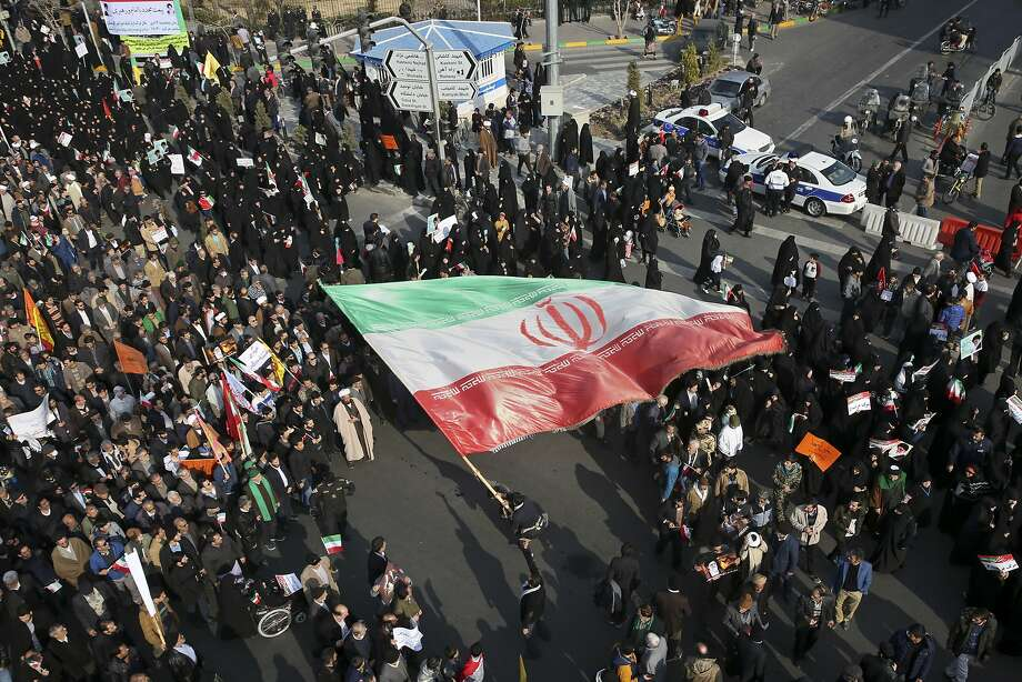 A demonstrator waves a huge Iranian flag during a pro-government rally in the northern city of Mashhad. Photo: Nima Najafzadeh, Associated Press