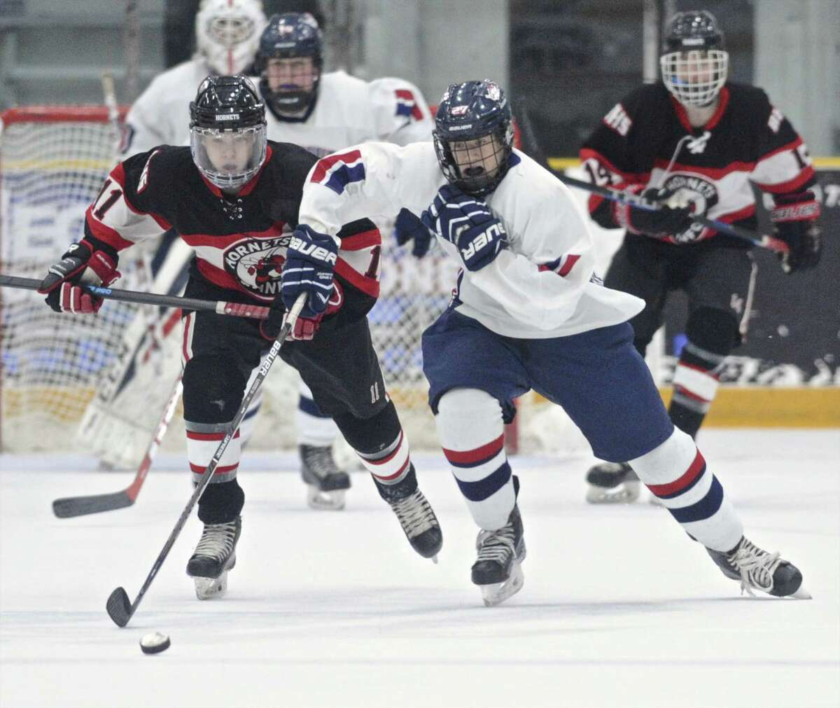 NFI's Zack Conboy (27) races for the puck ahead of Branford's Jack Manware (11) in the boys high school hockey game between Branford and NFI (New Fairfield/Immaculate high schools), Wednesday, February 8, 2017, at Danbury Ice Arena, in Danbury, Conn..
