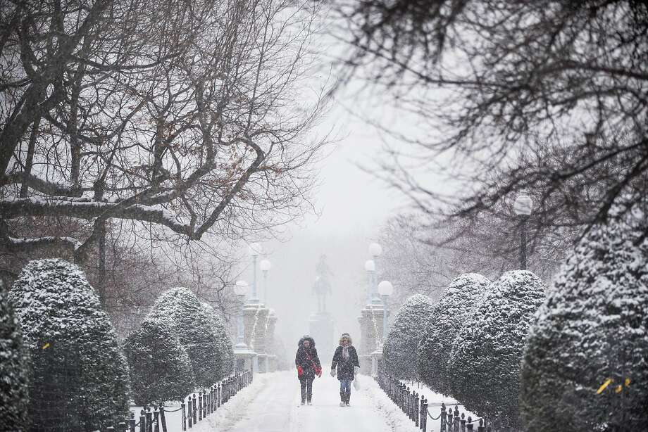 Pedestrians walk past the George Washington Statue in the Boston Public Garden. Boston expected a low around minus 11 overnight Saturday into Sunday from the massive winter snow storm. Photo: Adam Glanzman, Bloomberg