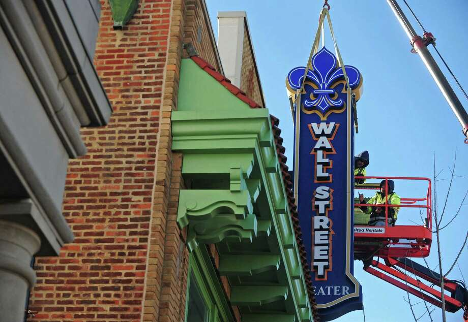 Workers with ABC Signs hang the new sign for the Wall Street Theater on Wall Street in Norwalk.The theater opened in May of this year and offers a variety of live entertainment. Photo: Erik Trautmann / Hearst Connecticut Media / Norwalk Hour
