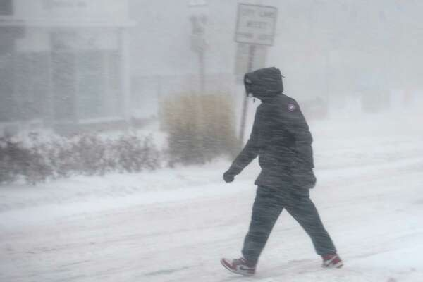 A man crosses Broad Street during the snowstorm in downtown Stamford, Conn. on Thursday, Jan. 4, 2018. Snow began early Thursday morning and is continuing throughout the day, coupled with heavy winds and low visibility.