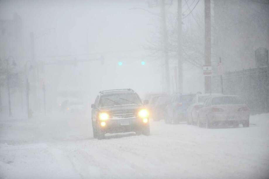 A car slowly drives down Pacific Street during the snowstorm in Stamford, Conn. on Thursday, Jan. 4, 2018. Snow began early Thursday morning and is continuing throughout the day, coupled with heavy winds and low visibility. Photo: Michael Cummo, Hearst Connecticut Media / Stamford Advocate