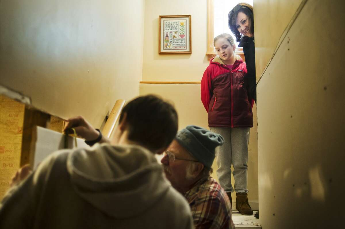 Katie Vokal of Midland, right, a case worker with the Flood Recovery Project, and her daughter Reagan, 10, watch as a group works to install drywall inside the home of Mike Lacusta and his family on Thursday, Dec. 28, 2017 in Midland. Volunteers from Chesaning United Methodist Church, working through the United Methodist Committee on Relief, helped to repair the Lacustas' basement, which was damaged by flooding in June. (Katy Kildee/kkildee@mdn.net)