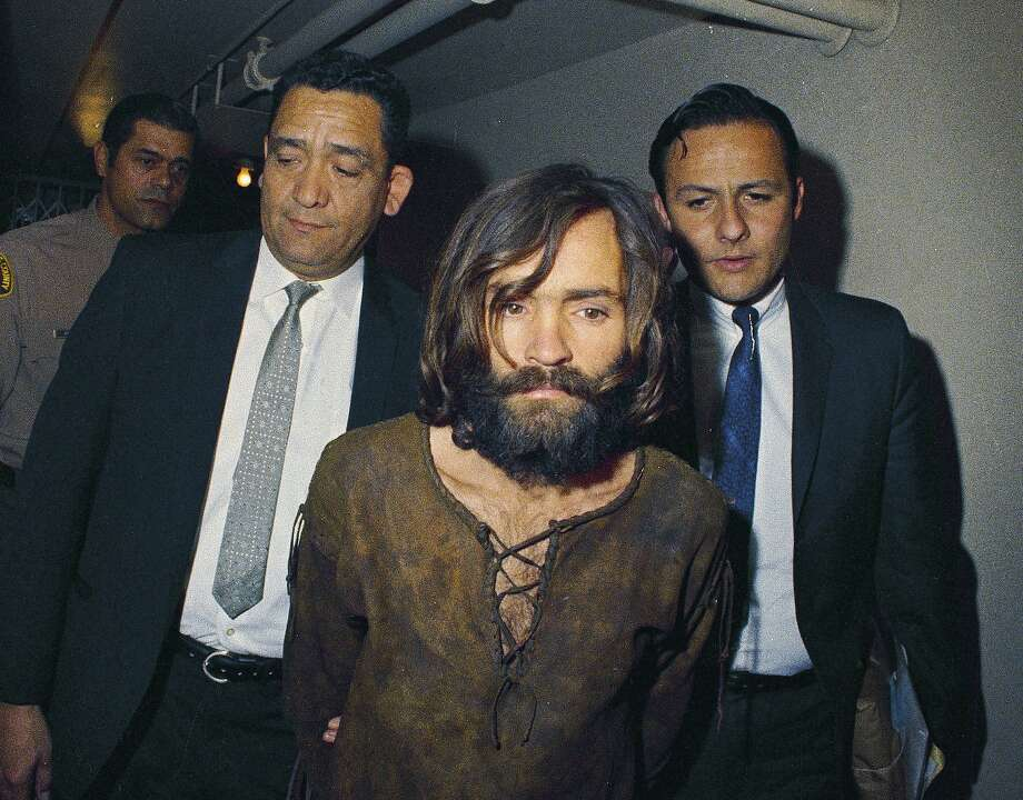 In this 1969 file photo, Charles Manson is escorted to his arraignment on conspiracy-murder charges in connection with the Sharon Tate murder case. The hippie cult leader who became the hypnotic-eyed face of evil across America after orchestrating the gruesome murders of the pregnant actress and six others in Los Angeles during the summer of 1969 was among the notable figures who died in 2017.  Photo: Associated Press