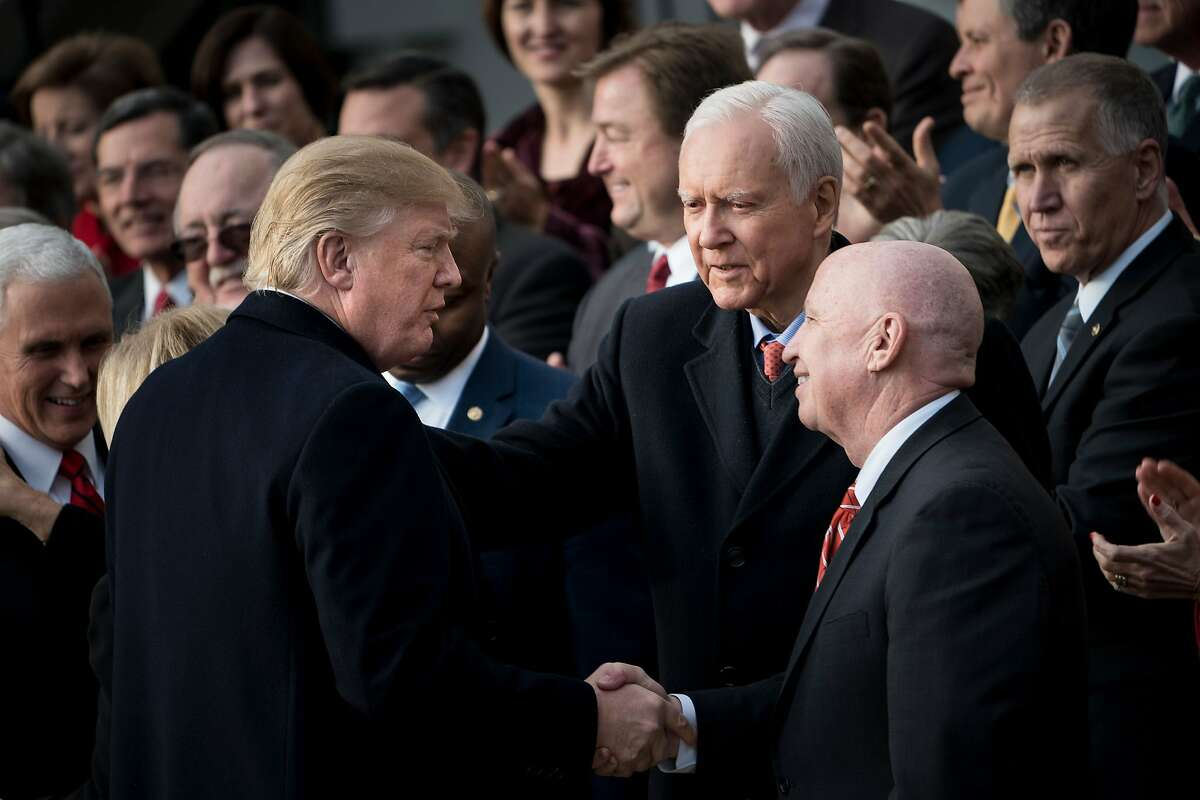 """(FILES) This file photo taken on December 20, 2017 shows US President Donald Trump (L) as he greets Senator Orrin G. Hatch(C) R-UT and Rep. Kevin Brady (R-TX) before speaking about newly passed tax reform legislation during an event in Washington, DC. Mitt Romney, who once ran for the US presidency against Barack Obama, appeared set for a political comeback on January 2, 2018 when veteran Republican Orrin Hatch said he is retiring from the US Senate. Hatch's announcement that he will not run in this year's mid-terms could spell bad news for President Donald Trump, who had encouraged him not to quit and clear the way for a Senate run by Romney, an outspoken critic who once dubbed Trump a """"fraud."""" / AFP PHOTO / Brendan SmialowskiBRENDAN SMIALOWSKI/AFP/Getty Images"""