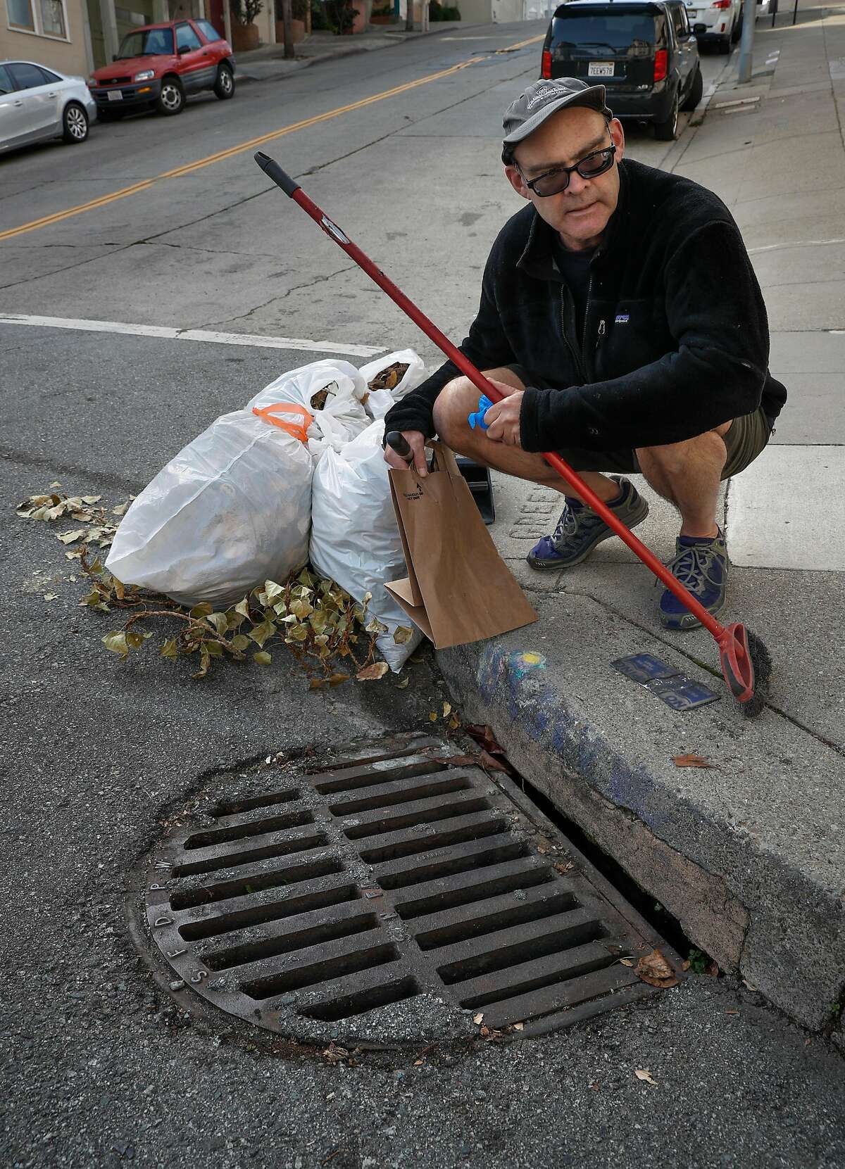"""Mark Cormier at the street drain he keeps clean to prevent clogging that leads to flooded streets near his Telegraph Hill home in San Francisco, Ca. as seen on Fri. December 22, 2017. The SFPUC is pushing to get more folks to """"adopt"""" sewer drains in order to prevent flooding."""