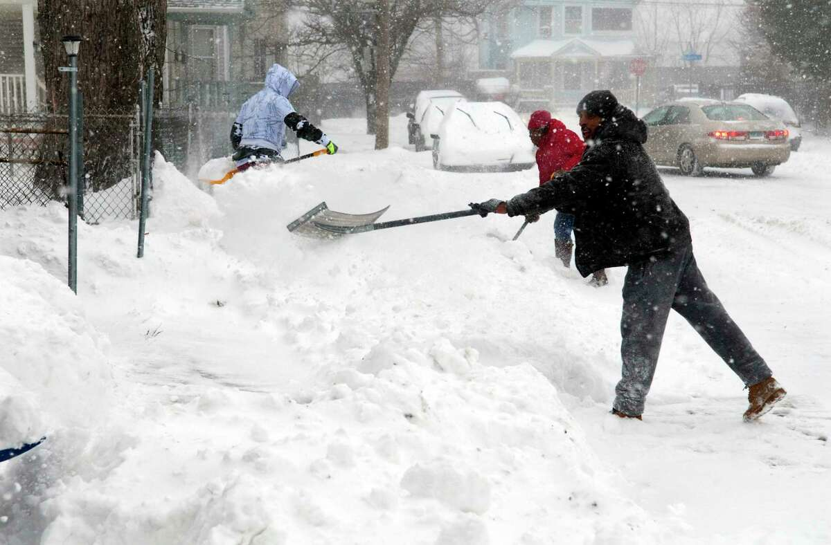 During a nor-easter that is pounding the region, Curtis Rushing shovels snow along with his neighbors at his home on Holly Street in Bridgeport, Conn., on Thursday Jan. 4, 2018.