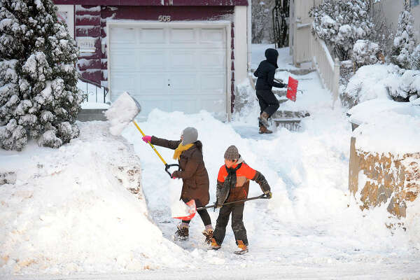 Maria Chavez and her family, son Brandon and daughter Camila begin to dig out their Hope Street home from a nor-easter that drop several inches of snow in Stamford, Conn. on Thursday, Jan. 4, 2018.