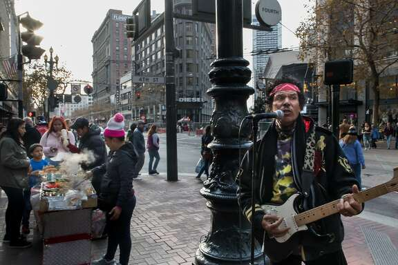 Robert Moses (right) asks the band with guitarist/vocalist Victor Hernanez to participate in The Bootstrap Project which will show street performers in February as they preform at Market Street on Saturday, Dec. 30, 2017 in San Francisco, Calif.