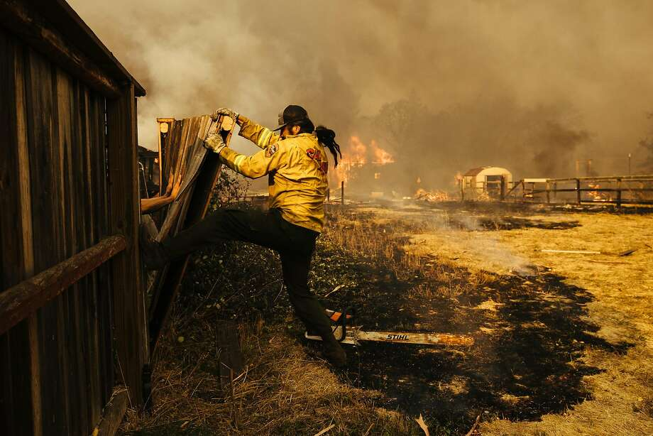 Firefighters knock down a fence in Santa Rosa during the Wine Country blazes in October. Photo: Mason Trinca, Special To The Chronicle