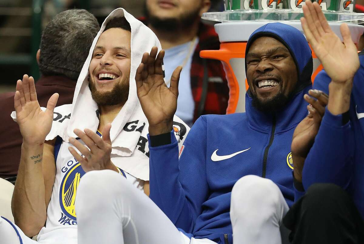 (L-R) Stephen Curry #30 and Kevin Durant #35 of the Golden State Warriors share a laugh during play against the Dallas Mavericks at American Airlines Center on January 3, 2018 in Dallas, Texas.