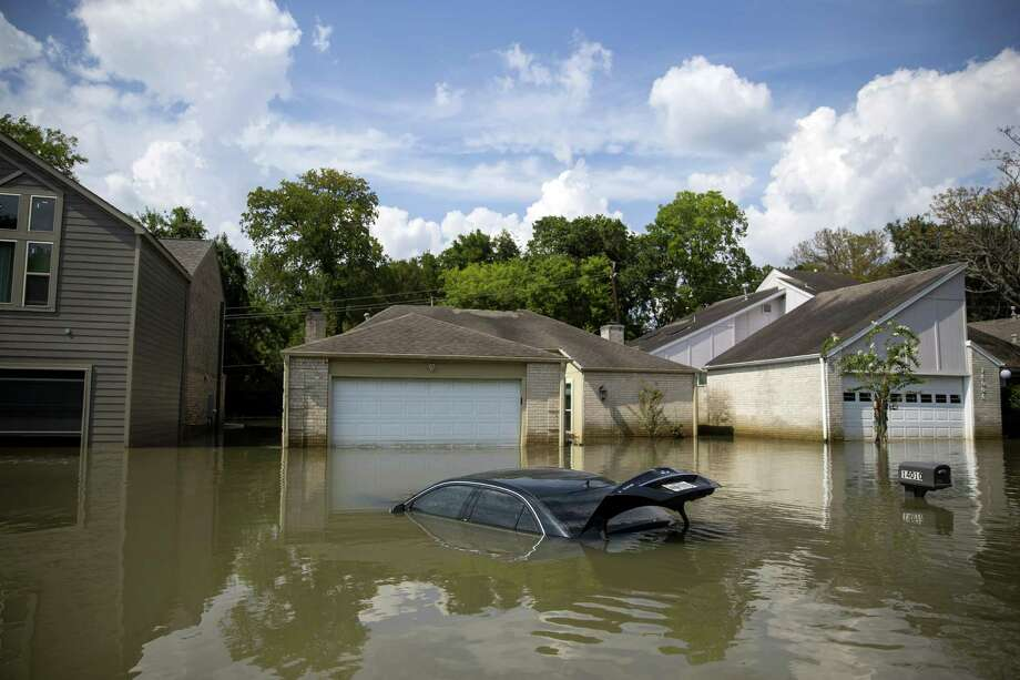 Homes and a car are inundated by floodwaters on Briarhills Parkway, in an upscale development in Houston on Sept. 5. There are effort to fit a cotton measure into disaster legislation. It shouldn't be there. Photo: ERIC THAYER /NYT / NYTNS