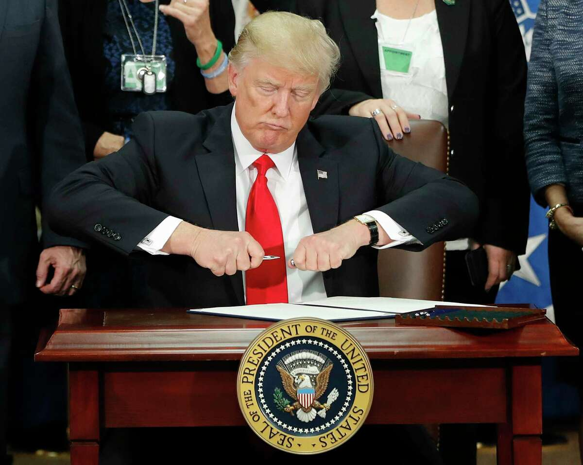On Wednesday, Jan. 25, 2017, President Donald Trump signs an executive order to cut off federal funding for so-called