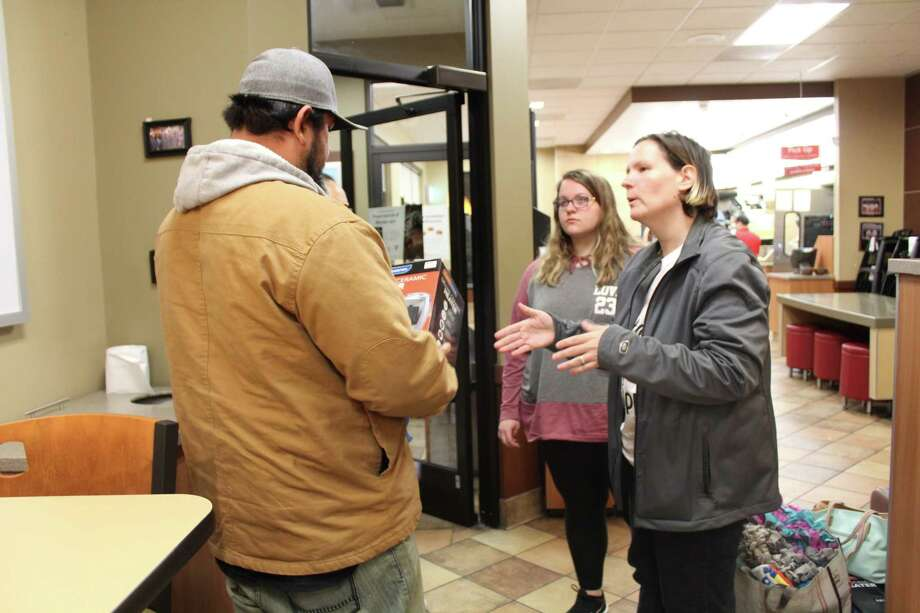 Sandy Adams provides Javier Martinez with a space heater and warm clothes at the Chick-Fil-A on Northpark Drive on a cold January day. Photo: Melanie Feuk