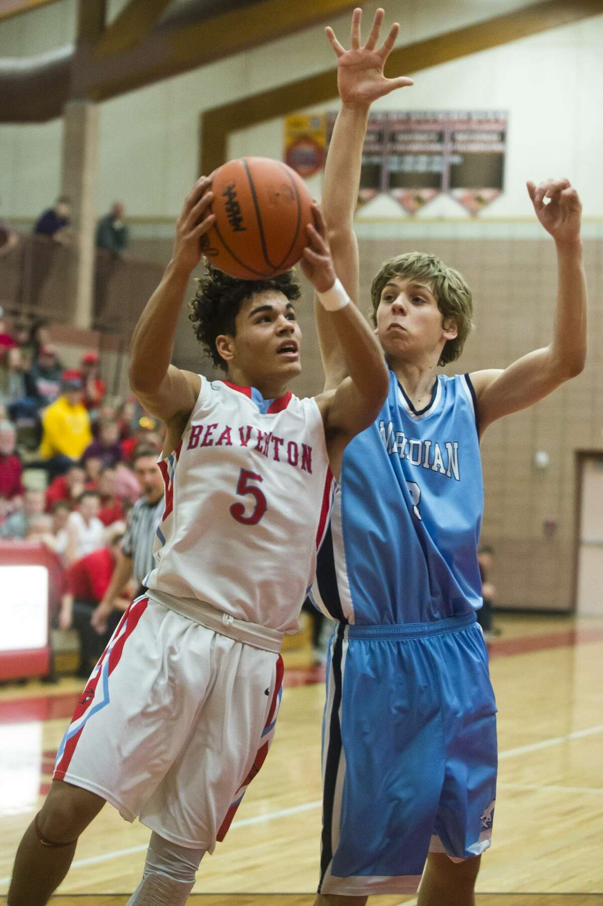 Beaverton senior Nate Taylor takes a shot as Meridian junior Lucas Lueder guards him during their game on Thursday, Jan. 4, 2018 at Beaverton High School. (Katy Kildee/kkildee@mdn.net)