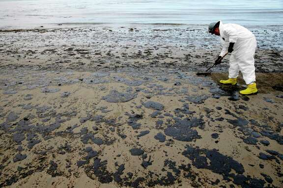 FILE - In this May 21, 2015 file photo, a worker removes oil from the sand at Refugio State Beach in the Santa Barbara Channel, north of Goleta, Calif., as cleanup work continues one month after the May 19 oil spill north of Santa Barbara, Calif. The Trump administration on Thursday, Jan. 4, 2018 moved to vastly expand offshore drilling from the Atlantic to the Arctic oceans with a plan that would open up federal waters off the California coast for the first time in more than three decades. The Channel is one of those areas. (AP Photo/Jae C. Hong, File)