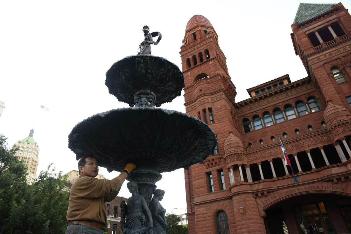 Gilbert E. Barrera uses steel wool on the 121-year-old fountain in front of the old Bexar County Courthouse, where he is refurbishing the fountain and the statue of Lady Justice, which he created and stands atop the fountain on Tuesday, Oct. 17, 2017.