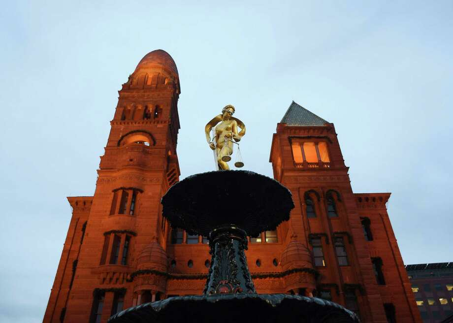 The Lady Justice statue atop a fountain in front of the Bexar County Courthouse gleams after being refurbished by artist Gilbert E. Barrera on Thursday evening, Jan. 4, 2017. Photo: Billy Calzada, Staff / San Antonio Express-News