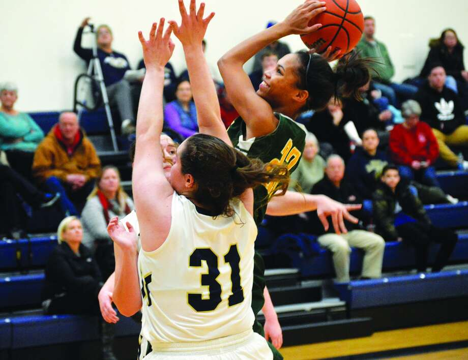 Metro-East Lutheran forward Ellen Schulte, right, goes up for a shot between two Father McGivney defenders during third-quarter action on Thursday at FMCHS.