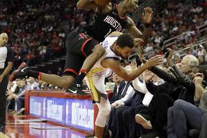 Houston Rockets' Trevor Ariza (1) collides with Golden State Warriors' Stephen Curry as recording artist Usher, right, extends his arms during the second half of an NBA basketball game Thursday, Jan. 4, 2018, in Houston. (AP Photo/David J. Phillip)