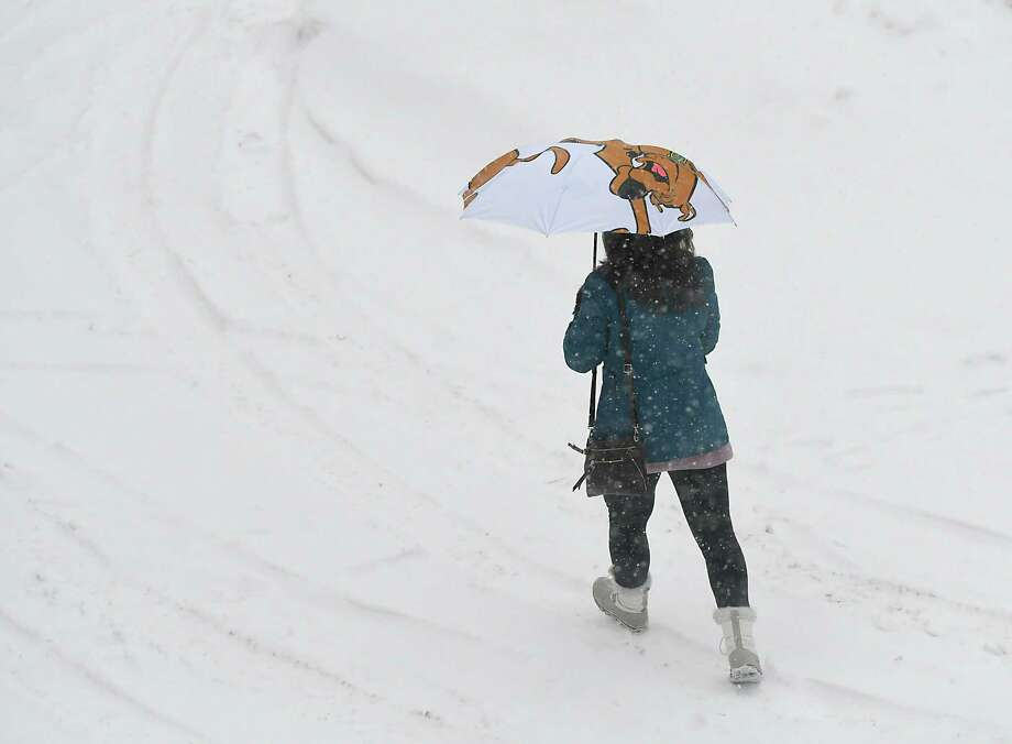 A woman uses an umbrella to protect her from the snow during a snow storm on Thursday, Jan. 4, 2018 in Troy, N.Y. (Lori Van Buren / Times Union) Photo: Lori Van Buren / 20042563A