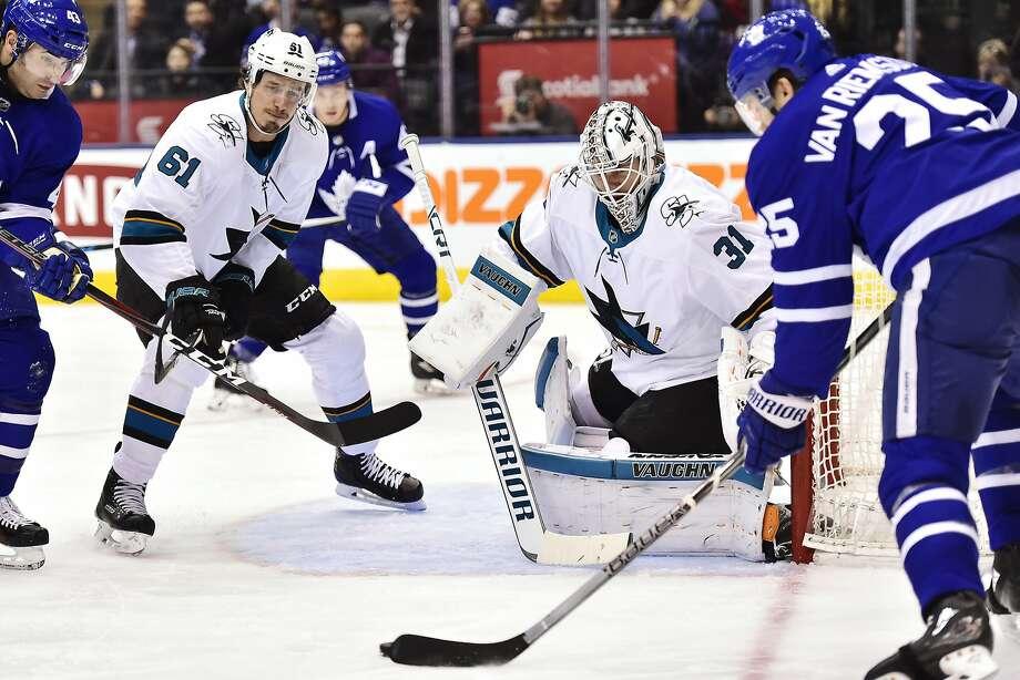 Maple Leafs' James van Riemsdyk (25) shoots on Sharks goalie Martin Jones (31) as the Sharks' Justin Braun (61) watches. Photo: Frank Gunn, Associated Press