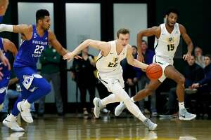 USF's Chase Foster (22) dribbles up court ahead of Nate Renfro (15) and BYU's Yoeli Childs in 1st half during men's college basketball in San Francisco, Calif., on Thursday, January 4, 2018.