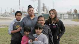 Sarahi Tovar is in her Manchester front yard with her  children, from left, Abraham, 11, Marisa, 5, Marion, 7, Camila, 8, and Dalila, 16. Their house is across the street from a refinery.