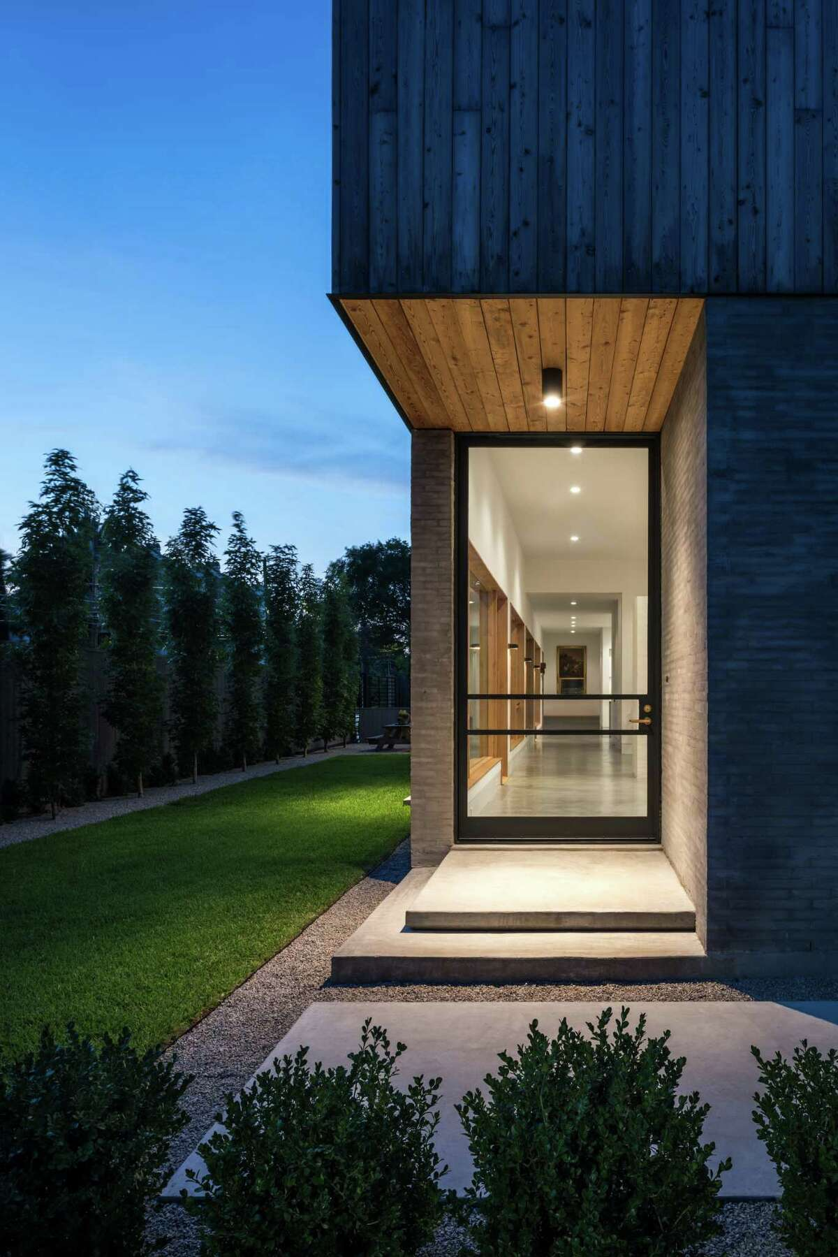 The home's custom front door is made of laser-cut steel and glass.