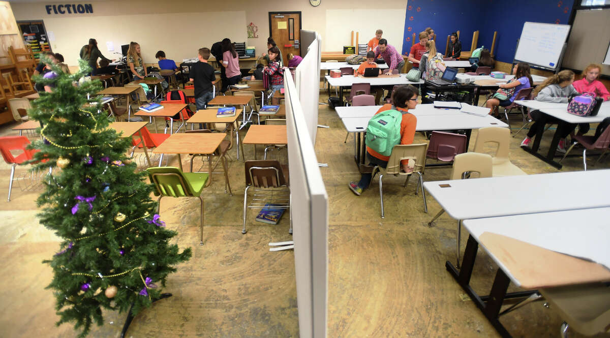Separated by a partition, two Orangefield Junior High classes share the library at Orangefield High School Tuesday. Students and faculty are finding work stations were they can due to damage from Tropical Storm Harvey. Photo taken Tuesday, December 19, 2017 Guiseppe Barranco/The Enterprise