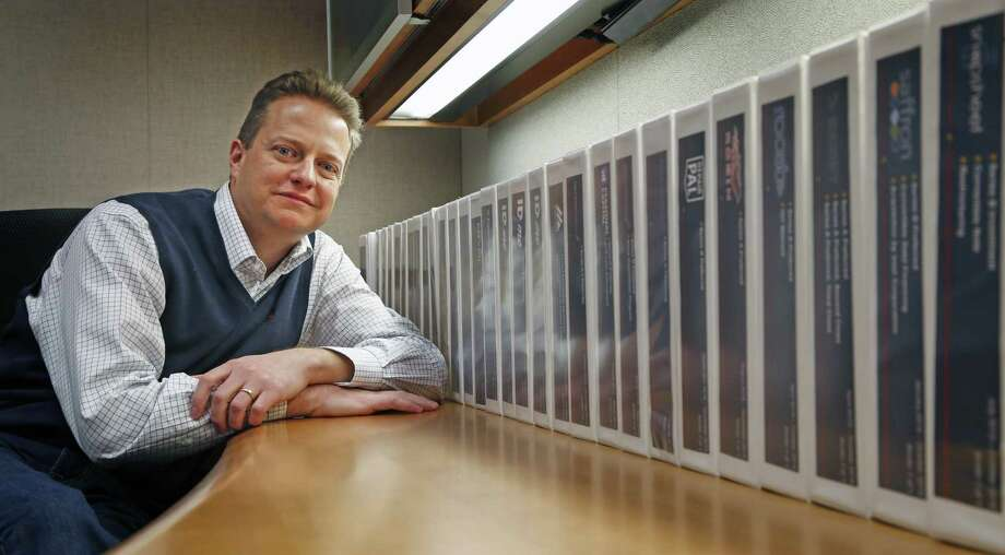 Nate McKinley, head of USAA's Corporate Development, which invests in fledgling companies that offers products and services that benefit the San Antonio company's customers. McKinley is pictured with USAA's deal binders for each of its investments. Photo: Ron Cortes /