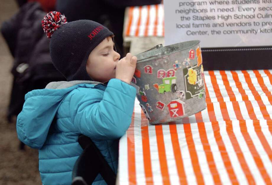 Johnny Williams, 3, of New Canaan, plays with a pail full of stickers during the Westport Winter Farmers' Market at Gilbertie's Herb and Garden Center in Westport on Dec. 30. Photo: Christian Abraham / Hearst Connecticut Media / Connecticut Post