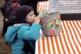 Johnny Williams, 3, of New Canaan, plays with a pail full of stickers during the Westport Winter Farmers' Market at Gilbertie's Herb and Garden Center in Westport on Dec. 30.