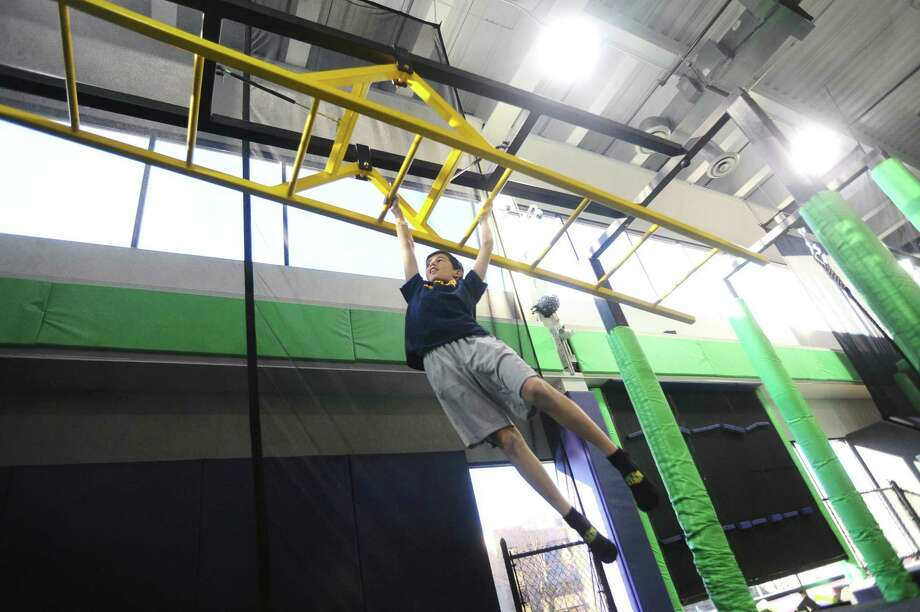 Twelve-year-old Beck Miller, of Darien, swings across monkey bars inside the Get Air Trampoline Park off Hope Street in Stamford on Dec. 26. Photo: Michael Cummo / Hearst Connecticut Media / Stamford Advocate