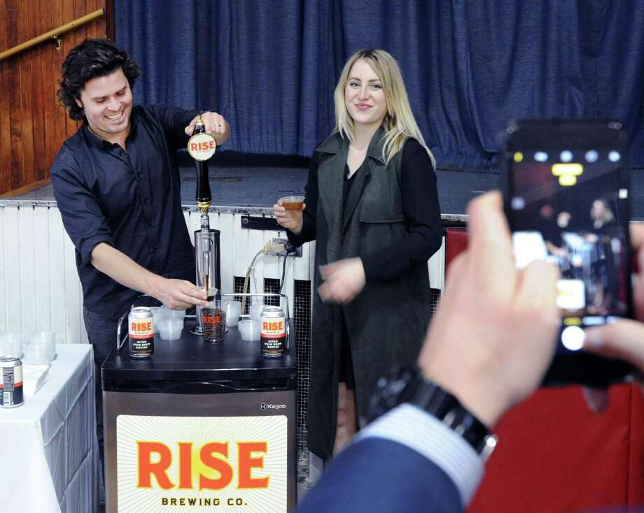 Jarrett McGovern and Paige Heeter of Rise Brewing serve up samples in April 2017 at the Greenwich Chamber of Commerce Business Showcase in Old Greenwich, Conn. Photo: Bob Luckey Jr. / Hearst Connecticut Media / Greenwich Time