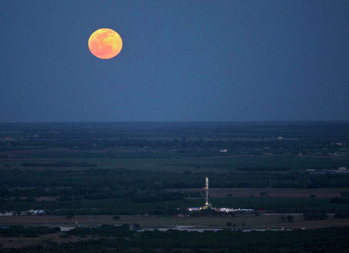 An Eagle Ford truck driver was sentenced Wednesday to 33 months in federal prison for his role in a scheme to steal almost $2 million of oil from companies operating in the Eagle Ford Shale. Pictured is a full moon rising above an oil drilling rig in 2014 near Karnes City.