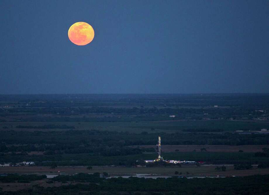 The full moon rises above an oil drilling rig Wednesday, May 14, 2014 in an aerial image taken near Karnes City, Texas. The first Eagle Ford well was drilled in La Salle County in late 2008, setting off a leasing and drilling frenzy across South Texas. The field pumps 1.2 million barrels per day now. Photo: William Luther /San Antonio Express-News / © 2014 San Antonio Express-News