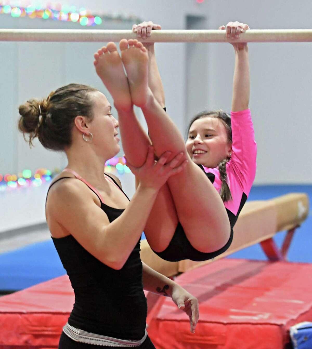 Megan Kennedy, 25, works with 8-yr-old Brooke Hakkinen in DC Stars Gymnastics Academy on Thursday, Dec. 21, 2017 in Watervliet, N.Y. Kennedy, a gymnast who grew up training at DC Stars Gymnastics Academy, is now the owner. (Lori Van Buren / Times Union)