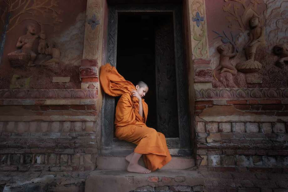 "A novice Buddhist monk in Laos' ancient city of Luang Prabang, a UNESCO World Heritage site. ""Voluntourists"" can help Laotians there work on their English. Photo: Undefined Undefined, Contributor / This content is subject to copyright."