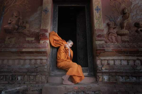 "A novice Buddhist monk in Laos' ancient city of Luang Prabang, a UNESCO World Heritage site. ""Voluntourists"" can help Laotians there work on their English."