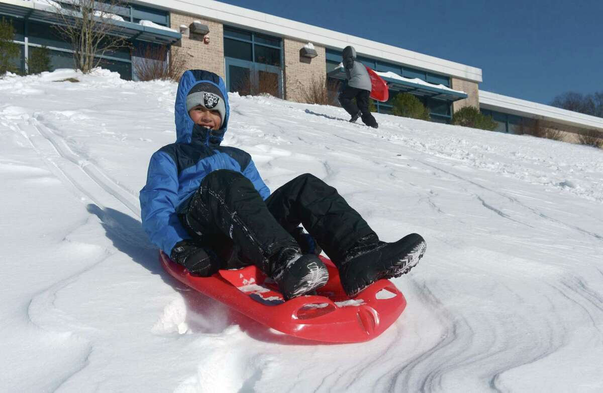 Justin Moldanado, 9, sleds with his brother at Naramake Elementary School Friday following Thursday's snowstorm.
