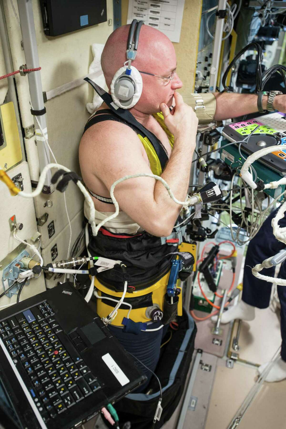 NASA astronaut Scott Kelly, wearing a headset and a Chibis Lower Body Negative Pressure (LBNP) Suit, undergoes ultrasound measurements for the Fluid Shifts experiment.