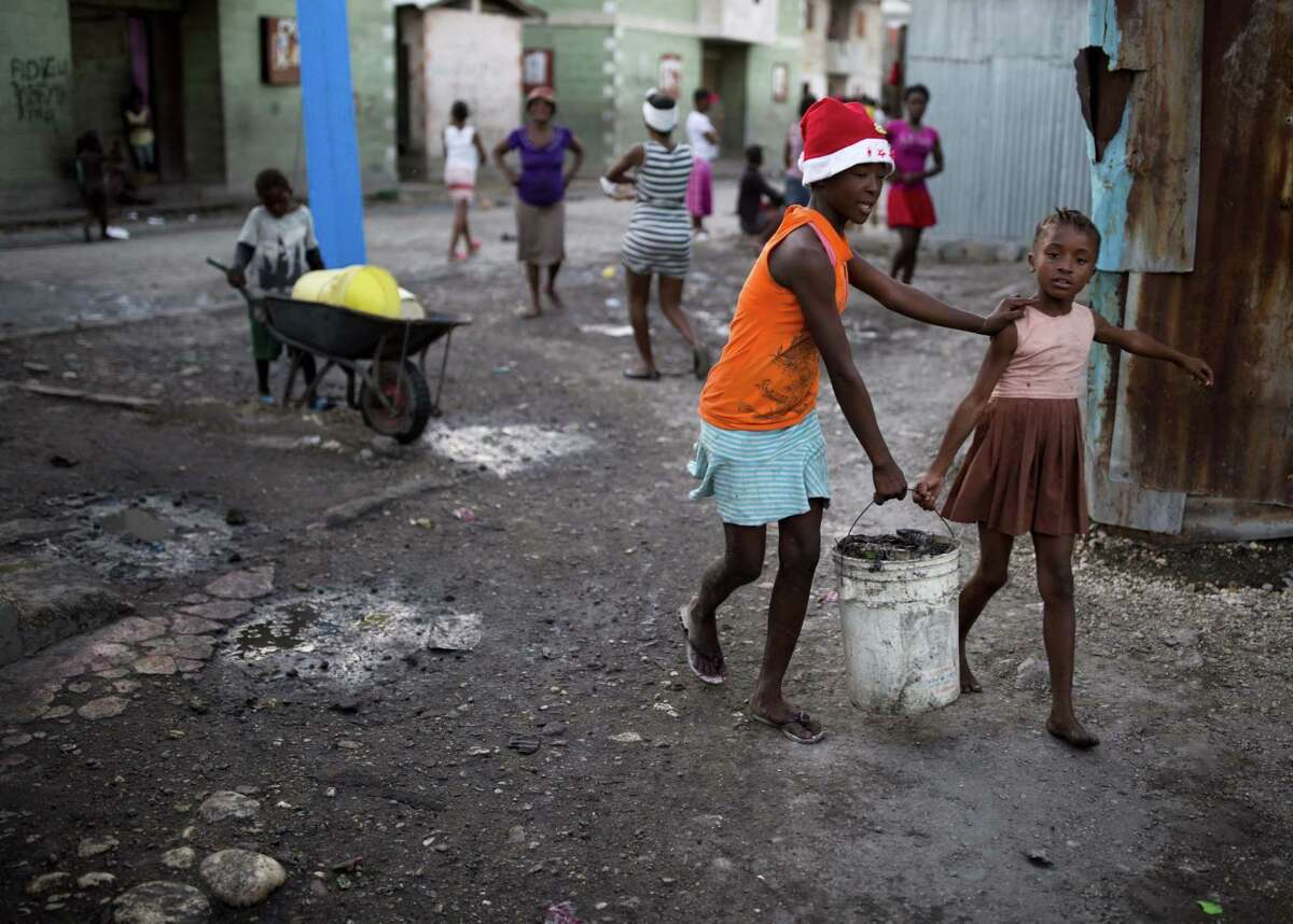 Children carry a bucket of trash to a dump in a Port-au-Prince, Haiti, slum. The inability of poverty-stricken parents to adequately feed and educate their children has made Haiti a hub for human trafficking.