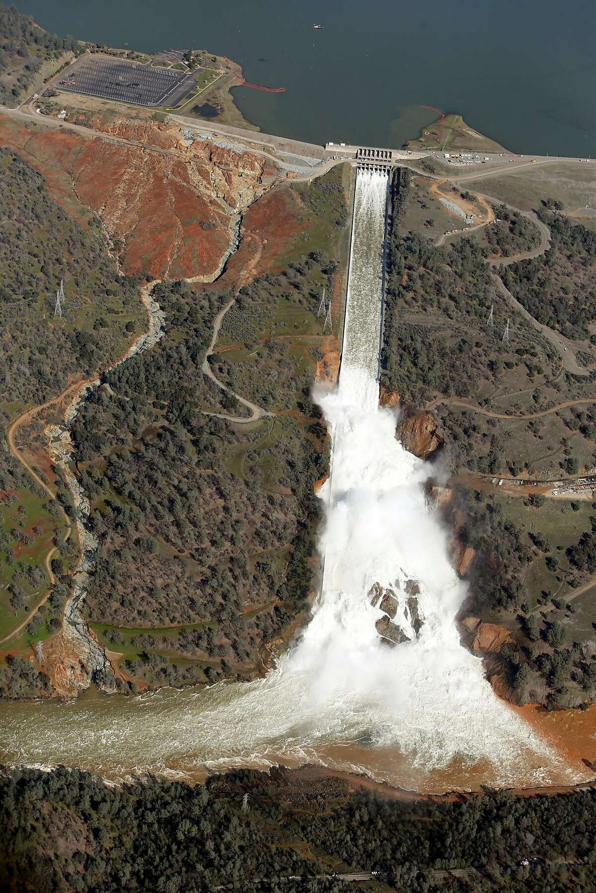 Water flows out of the damaged spillway at Oroville Dam in Oroville, Calif., on Tuesday, February 14, 2017. State water officials say they've met their Nov. 1 deadline for rebuilding the dam's two damaged spillways, but federal officials are skeptical that the repaired spillways can handle a big flood.