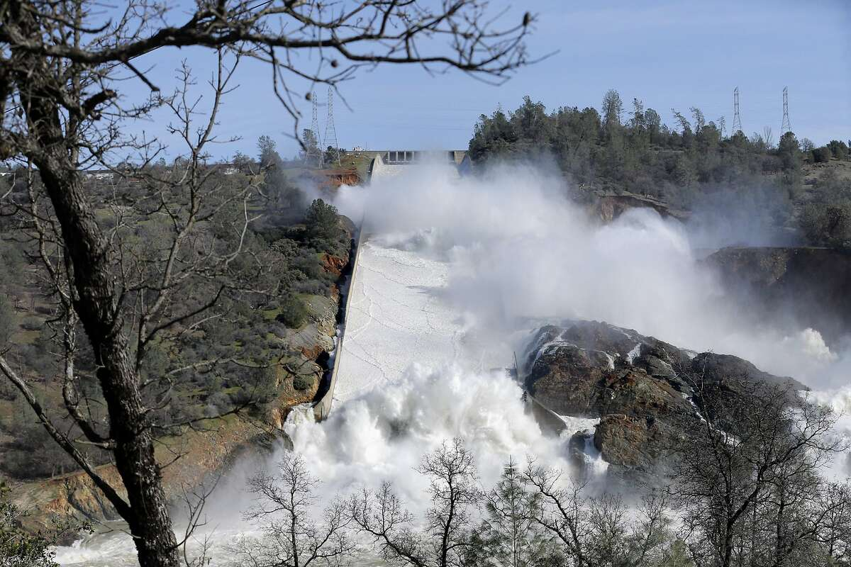 Thousands of gallons of water rush over the main and auxiliary spillway at Oroville Dam in Oroville, Calif., on Sunday, February 12, 2017. The California Department of Water Resources is now working to remove debris from the river so water flow down the Feather River doesn't impede the hydroelectric generation at the dam.