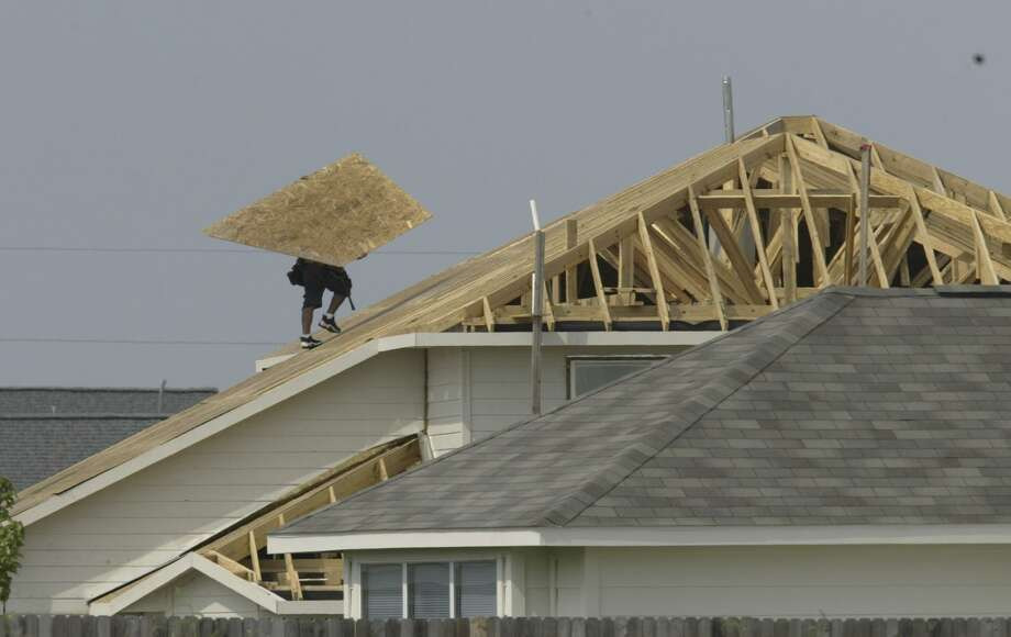 A worker completes a roof in the Houston area in 2004. Today, property taxes in Texas are forcing many residents to move outside cities or their longtime neighborhoods in search of financial relief. Photo: File Photo /Houston Chronicle / Aaron M. Sprecher