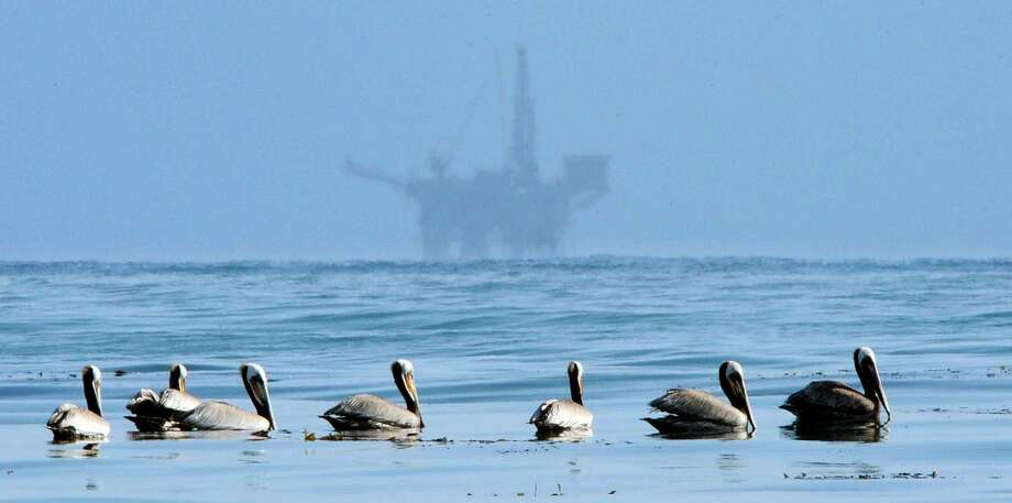 FILE - In this May 13, 2010 file photo, pelicans float on the water with an offshore oil platform in the background in the Santa Barbara Channel off the coast of Santa Barbara, Calif. The Trump administration on Thursday, Jan. 4, 2018 moved to vastly expand offshore drilling from the Atlantic to the Arctic oceans with a plan that would open up federal waters off the California coast for the first time in more than three decades. The Channel is one of those areas. (AP Photo/Mark J. Terrill, File) Photo: Mark J. Terrill, STF / AP2010