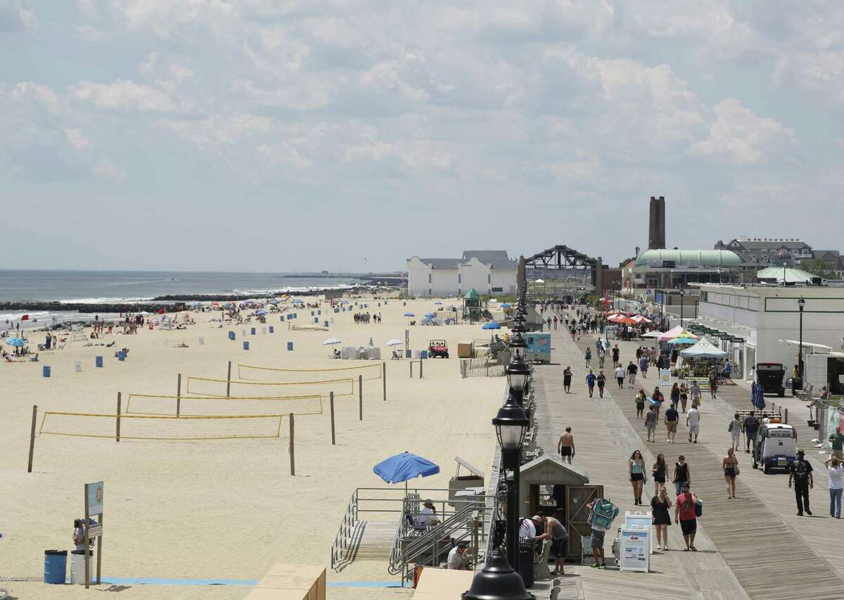 In this June 21, 2017, photo, people walk along the boardwalk in Asbury Park, N.J. New Jersey Gov.-elect Phil Murphy, other political and environmental leaders, pledged to help lead opposition to President Trump's plan to open virtually the entire U.S. coastline to oil and gas drilling, saying the effects of a spill would be far worse than those of medical waste washups in the 1980s that cost New Jersey's tourism industry an estimated $1 billion in losses.