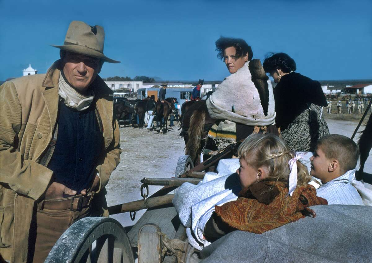 In costume (as Colonel Davy Crockett), American actor John Wayne (1907 - 1979) (left) directs unidentified cast members in a scene from their film 'The Alamo', Brackettville, Texas, 1960. (Photo by Tom Nebbia/Corbis via Getty Images)