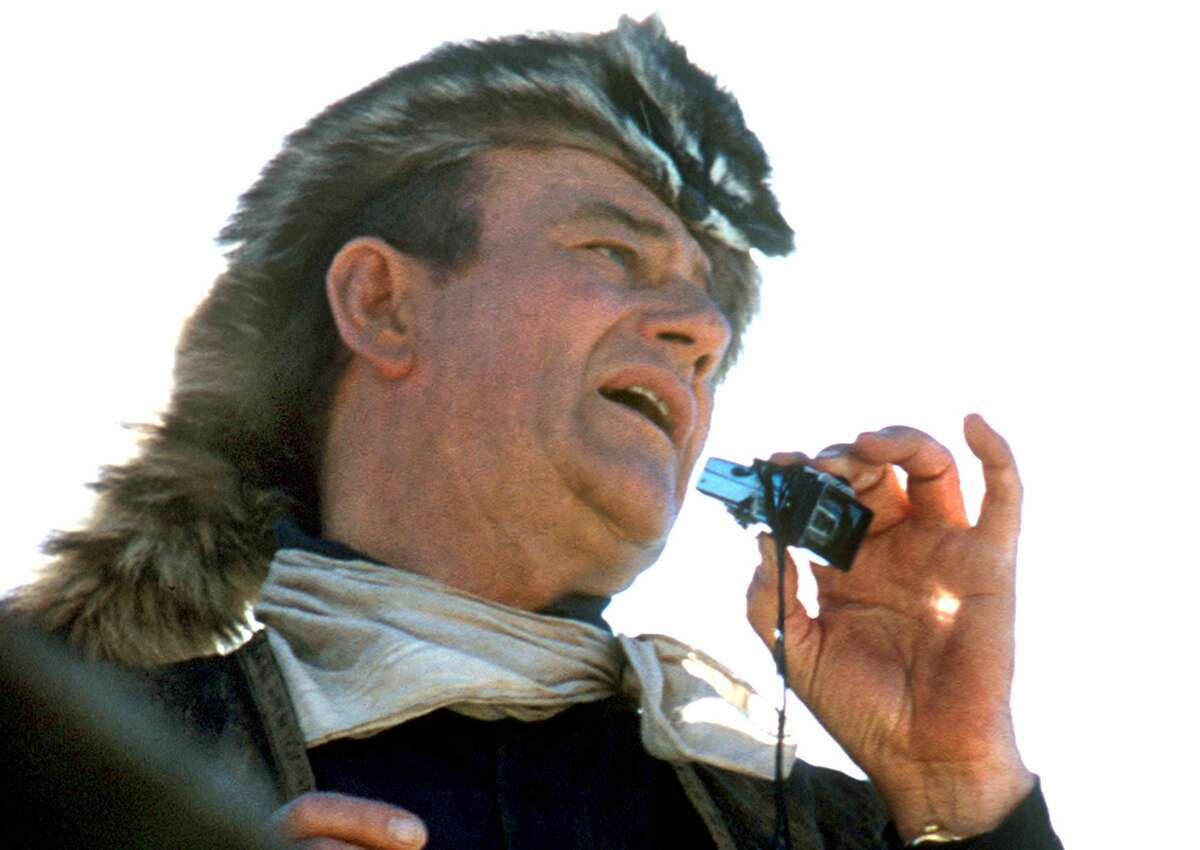 Low-angle view of American actor John Wayne (1907 - 1979) (in costume as Colonel Davy Crockett) as he directs him film 'The Alamo', Brackettville, Texas, 1960. (Photo by Tom Nebbia/Corbis via Getty Images)